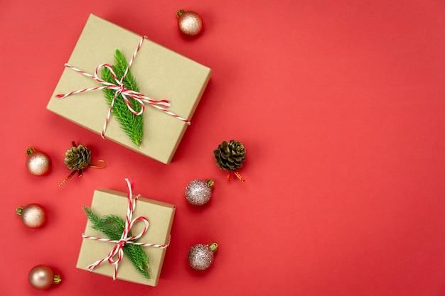 Vrolijke kerstversiering. plat lag essentiële verschil objecten geschenkdoos & fir tree op modern rood papier