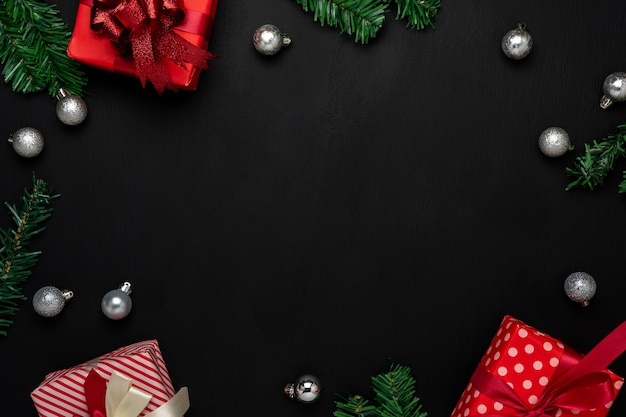 Vrolijke kerstversiering. plat lag essentiële verschil objecten geschenkdoos & fir tree op modern zwart papier