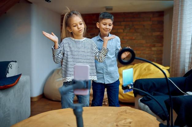 Vrolijke kinderbloggers dansen voor de camera, kleine vloggers
