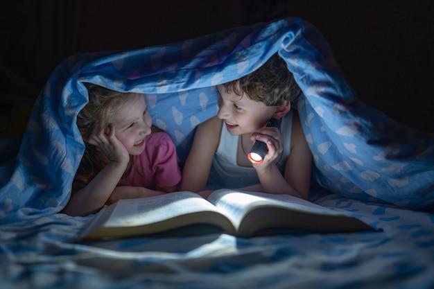 Vrolijke kinderen, broer en zus liggen onder de dekens en lezen een boek
