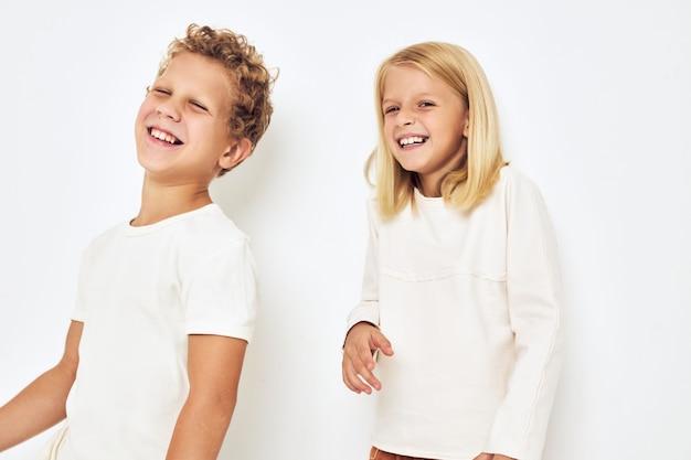 Vrolijke kinderen dansen glimlach poseren vrijetijdskleding geïsoleerde achtergrond. hoge kwaliteit foto