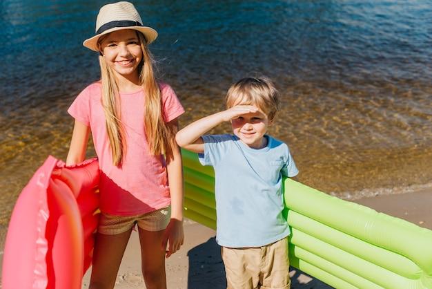 Vrolijke kinderen die in hete dag bij kust grijnzen