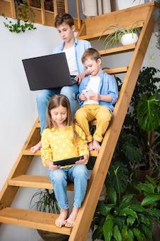 Vrolijke kinderen in vrijetijdskleding gebruiken gadgets, kijken naar de camera en glimlachen