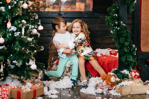 Vrolijke kinderen knuffelen in de studio met kerstboom en nieuwjaar decoraties.