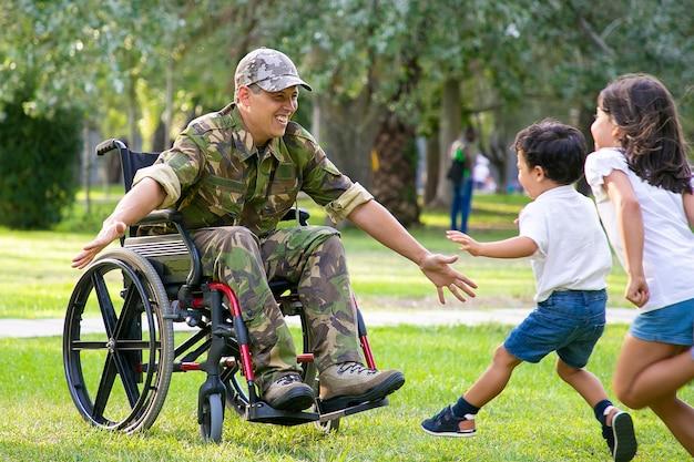 Vrolijke kinderen ontmoeten militaire vader en rennen naar gehandicapte man in camouflage met open armen voor knuffel. veteraan van oorlog of naar huis terugkeren concept