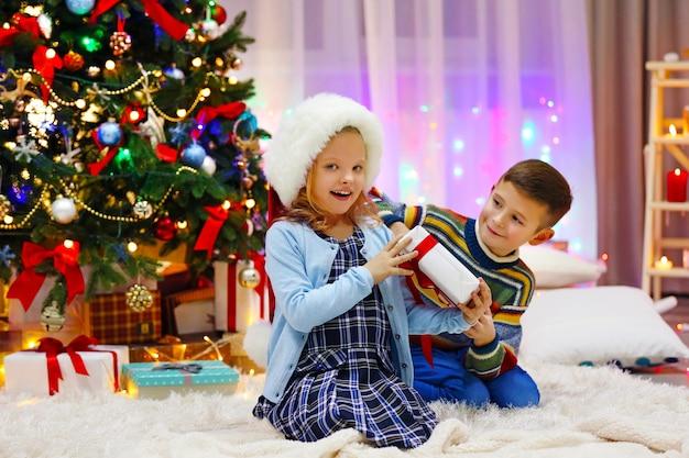 Vrolijke kinderen spelen met cadeautjes in de versierde kerstkamer