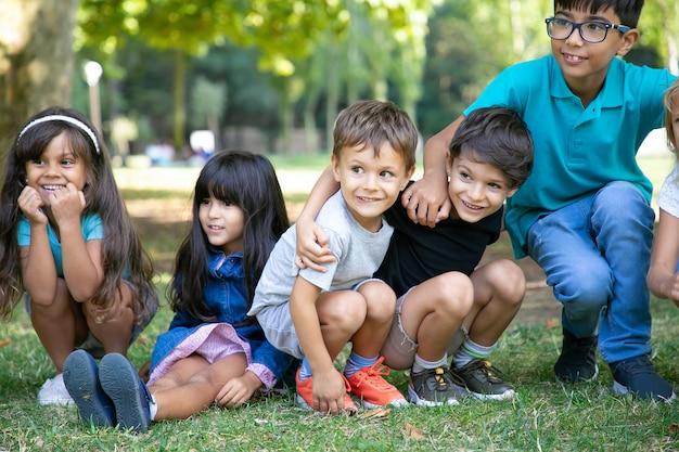 Vrolijke kinderen zitten en gehurkt op het gras, knuffelen elkaar en kijken opgewonden weg. kinderen spelen of entertainment concept
