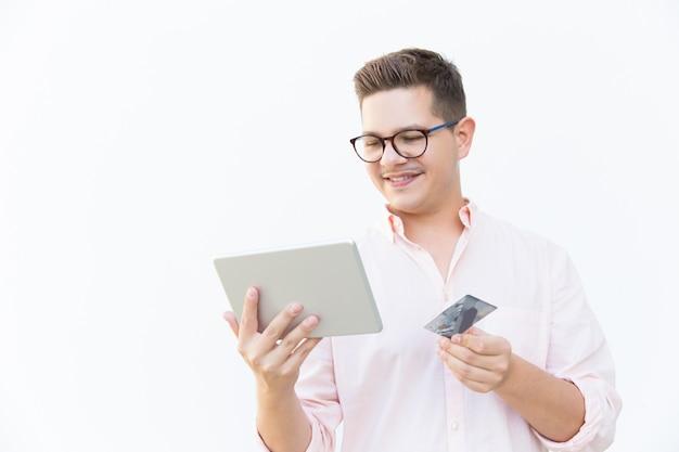 Vrolijke klant met tablet en creditcard online betalen