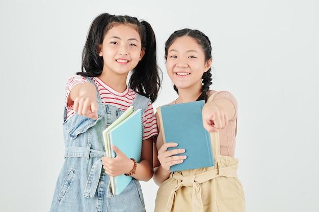 Vrolijke klasgenoten met leerboeken in handen glimlachen en wijzen