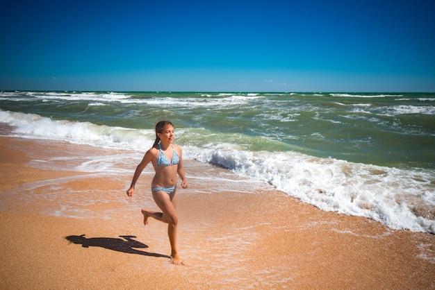 Vrolijke kleine actieve meisje springen op de golven van een stormachtige zee op een zonnige warme zomerdag