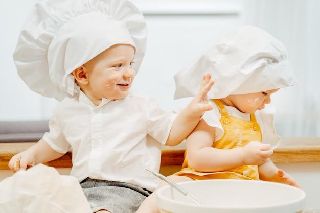 Vrolijke kleine blanke vrolijke kinderen broer en zus koken deeg voor knoedels zittend op de keukentafel. ouders helper kinderen concept