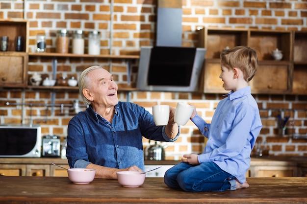 Vrolijke kleine jongen die thee drinkt tijdens het ontbijt met zijn grootvader
