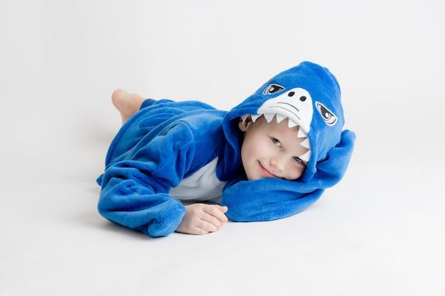 Vrolijke kleine jongen die zich voordeed op een wit in pyjama, blauw haaikostuum