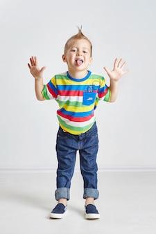 Vrolijke kleine jongen hamming en tonen van de tong
