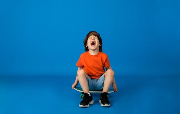 Vrolijke kleine jongen met bruin haar in een t-shirt en denim shorts zit op een skateboard op een blauwe ondergrond met ruimte voor tekst. straatsporten