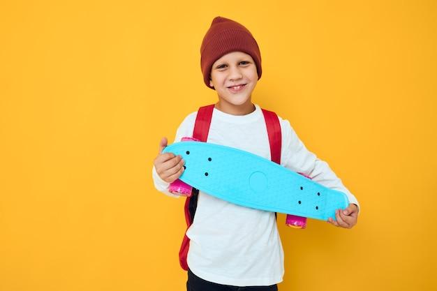 Vrolijke kleine jongen met rode rugzak blauwe skateboard gele kleur achtergrond