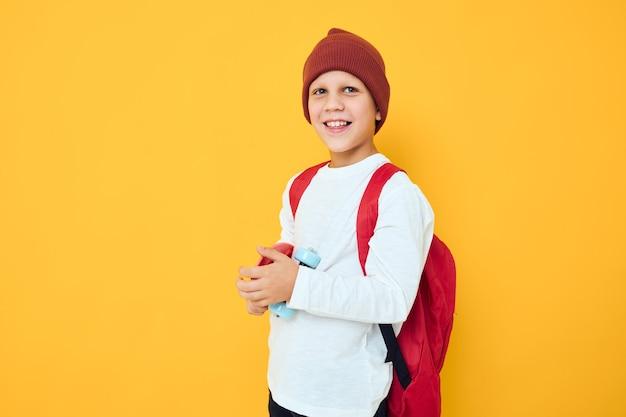 Vrolijke kleine jongen met rode rugzak rode skateboard gele kleur achtergrond