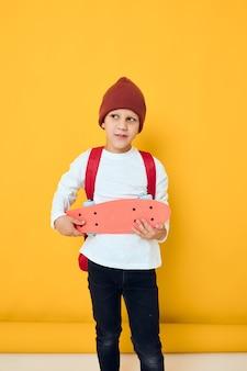 Vrolijke kleine jongen met rode rugzak rode skateboard jeugd lifestyle concept