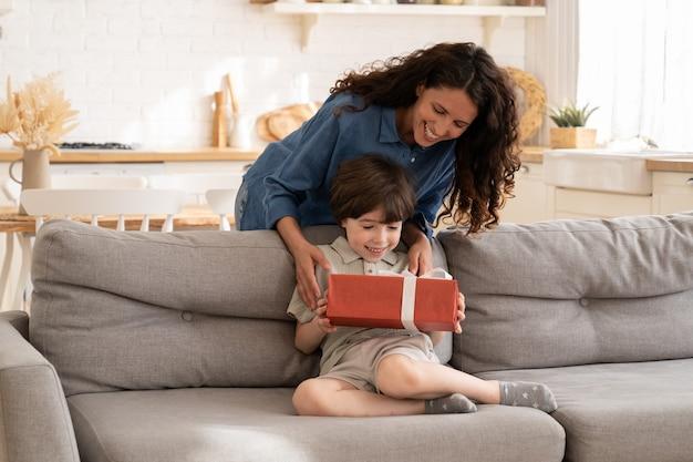 Vrolijke kleine jongen ontvangt verjaardagscadeau van mama die op de bank in de woonkamer zit en een geschenkdoos vasthoudt