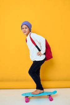 Vrolijke kleine jongen rijdt op een skateboard in een blauwe hoed jeugd lifestyle concept