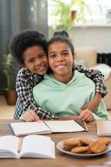 Vrolijke kleine jongen van gemengd ras die zijn gelukkige zus omhelst terwijl hij allebei aan tafel voor de camera zit en naar je kijkt met een brede glimlach