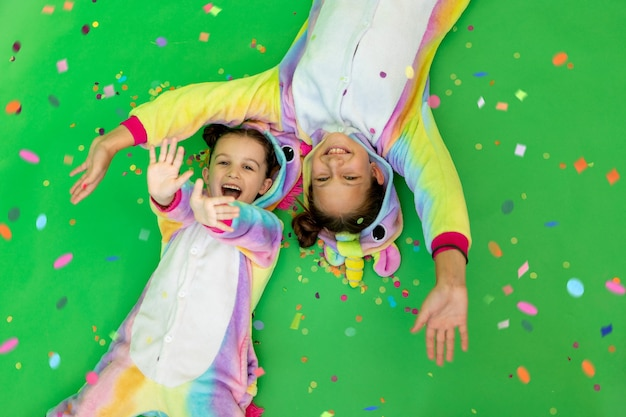 Vrolijke kleine meisjes in een eenhoornkostuum op een groene achtergrond