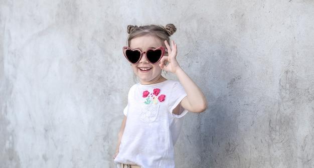 Vrolijke kleine meisjes op grijze gestructureerde achtergrond. outdoor portret meisje. grijze geweven muurachtergrond.