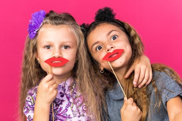 Vrolijke kleine mooie meisjes die valse lippen op stokjes houden die op roze muur met exemplaarruimte worden geïsoleerd