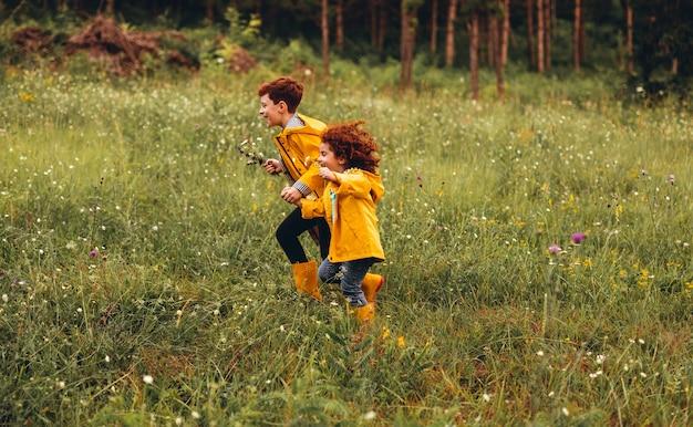 Vrolijke kleine roodharige zus en broer hand in hand en rennen