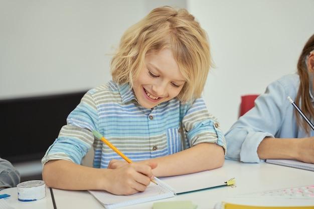 Vrolijke kleine schooljongen die lacht terwijl hij een potlood vasthoudt en aantekeningen maakt terwijl hij aan tafel studeert
