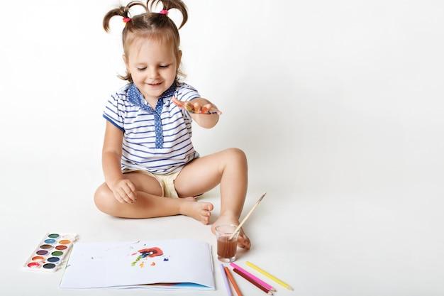 Vrolijke kleine vrouwelijke jongen tekent met aquarel, maakt vingerafdrukken, heeft alleen plezier, houdt van schilderen, geïsoleerd op wit. het creatieve meisje maakt kunstwerk, zijnde toekomstige schilder