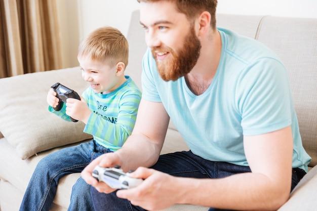 Vrolijke kleine zoon en vader die thuis samen computerspelletjes spelen en glimlachen