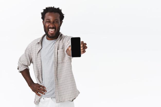Vrolijke knappe afro-amerikaanse bebaarde man in geruit overhemd