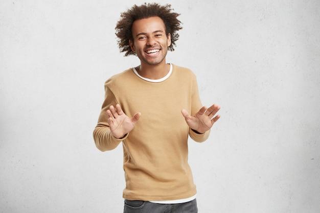 Vrolijke knappe afro-amerikaanse man heeft knapperig haar, nonchalant gekleed