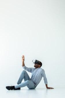 Vrolijke knappe afro-amerikaanse man zittend op de vloer terwijl hij een vr-bril draagt