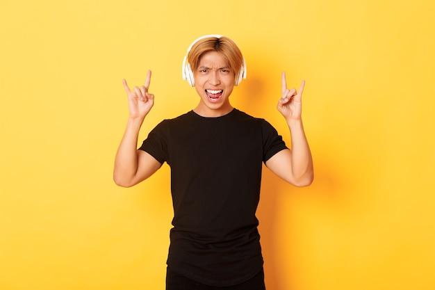 Vrolijke knappe aziatische kerel die geniet van het luisteren naar muziek in hoofdtelefoons, die rock-n-roll-gebaar toont, dat zich over gele muur bevindt