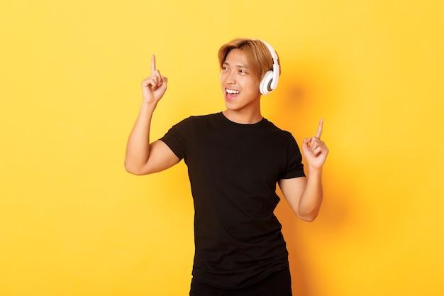 Vrolijke knappe aziatische man met blond haar, meezingend en dansen als luisteren naar muziek in draadloze koptelefoons, staande gele muur
