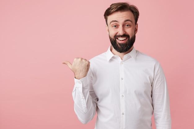 Vrolijke knappe bebaarde donkerbruine man met kort kapsel die gelukkig naar voren kijkt met een brede glimlach, hand met duim opstekend terwijl hij over roze muur staat