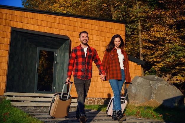 Vrolijke knappe bebaarde jonge man en mooie stijlvolle vrouw uitgaan van modern huis met koffers terwijl ze samen op vakantie gaan.