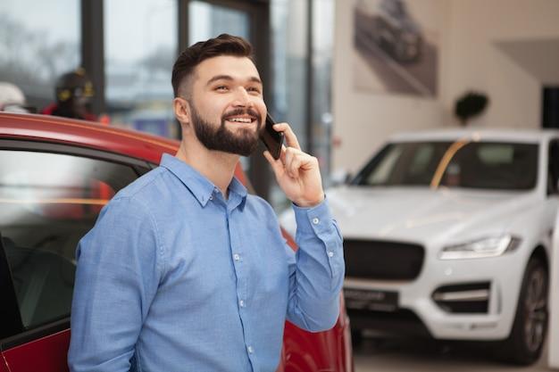 Vrolijke knappe bebaarde man glimlachend vrolijk, wegkijken tijdens het gesprek aan de telefoon bij autodealer, kopie ruimte