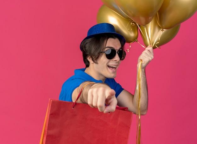 Vrolijke knappe blanke man in zonnebril met blauwe feestmuts houdt heliumballonnen en papieren boodschappentassen wijzend op de camera