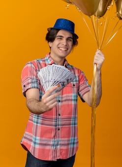 Vrolijke knappe blanke man met blauwe feestmuts houdt heliumballonnen en geld vast