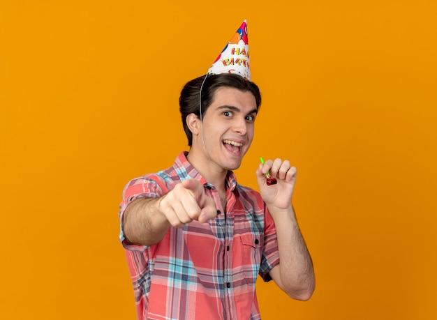 Vrolijke knappe blanke man met verjaardagspet houdt feestfluitje wijzend op camera