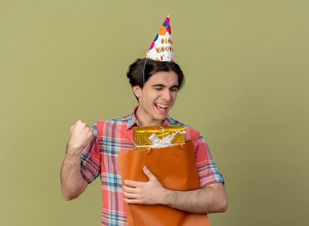 Vrolijke knappe blanke man met verjaardagspet houdt vuist en houdt geschenkdoos in papieren boodschappentas