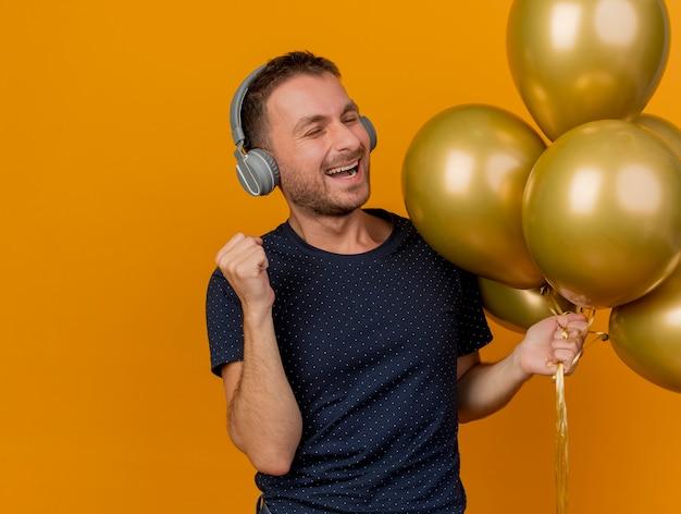 Vrolijke knappe blanke man op koptelefoon houdt helium ballonnen en houdt vuist geïsoleerd op een oranje achtergrond met kopie ruimte