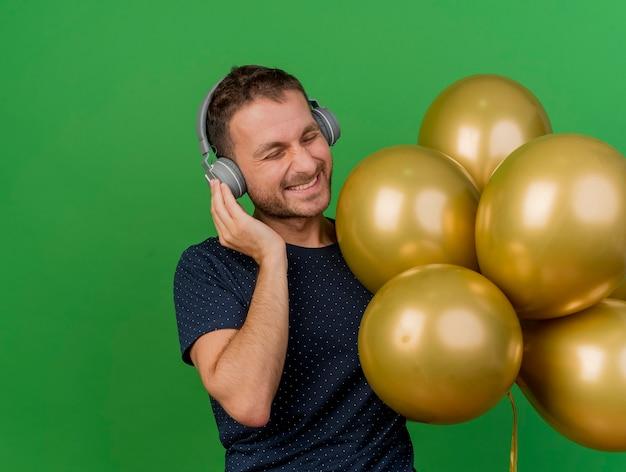 Vrolijke knappe blanke man op koptelefoon houdt helium ballonnen geïsoleerd op groene achtergrond met kopie ruimte