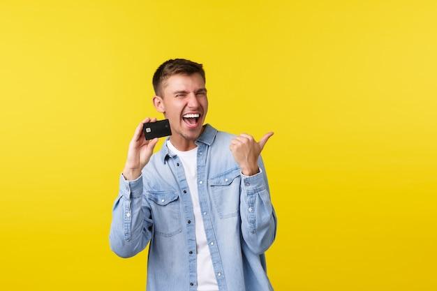 Vrolijke knappe blonde man die met de vinger naar rechts wijst en creditcard toont, lacht van vreugde, reclame maakt voor bankdiensten, geweldige prijzen in de winkel, gaat winkelen, staande gele achtergrond.