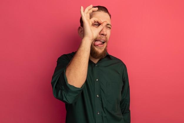 Vrolijke knappe blonde man steekt tong uit en kijkt naar voren door vingers geïsoleerd op roze muur