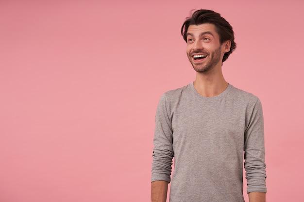 Vrolijke knappe donkerharige man met baard in grijze trui, staand, opzij kijkend met een brede glimlach, samentrekkend voorhoofd en opgetrokken wenkbrauwen