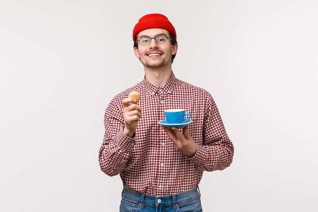 Vrolijke knappe en ontspannen jonge kaukasische bebaarde man genieten van zijn thee met koekjes, koekje en kopje te houden als het drinken van koffie tijdens de lunchpauze, tevreden glimlachen,